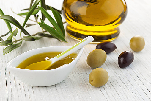 Olive oil and green and black olives on white